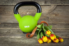 Modern kettlebells and tied with a measuring tape bouquet of tulips flowers on a wooden background. Royalty Free Stock Images