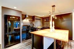 Modern keukenbinnenland in donkere bruin met zwarte toestellen Stock Foto