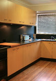 Modern Kitchen 1. Sleek and modern kitchen with wood cupboards and flooring Stock Photo