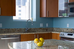 Modern kitchen. New modern kitchen interior with island in a condo apartment. Brightly lit, light blue walls, granite countertops, stainless steel appliances Royalty Free Stock Photography