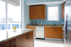 Modern kitchen. New modern kitchen interior with island in a condo apartment. Brightly lit, light blue walls, granite countertops, stainless steel appliances. A Stock Image