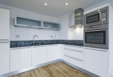 Modern kitchen. Modern white kitchen with built in appliances and mosaic decoration Stock Image