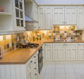 Modern Kitchen. A spacious modern cream kitchen with tiled walls Stock Image