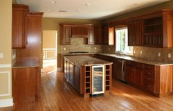 Modern Kitchen. With beautiful wooden cabinets, marble counter tops and hardwood floors royalty free stock photography