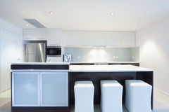 Modern kitchen. With stainless steel appliances and white chairs Stock Photo