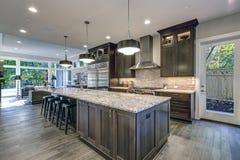 Modern kitchen with brown kitchen cabinets. Oversized kitchen island with bar stools, granite countertops, huge refrigerator and beige backsplash. Northwest stock images