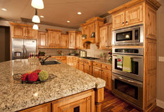 Modern Kitchen with Center Island. Modern home with lovely custom kitchen cabinets, countertops, stainless appliances and center island Royalty Free Stock Image
