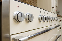 Modern kitchen cooker. Large range style cooker in modern kitchen interior with granite worktop and cream units Stock Images