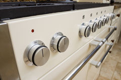 Modern kitchen cooker. Large range style cooker in modern kitchen interior with granite worktop and cream units Stock Image