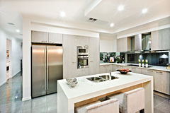 Modern kitchen counter top with a fridge and pantry. Giving a shiny look the house interior with flashing lights over the tile floor hallway stock photo