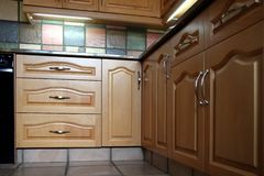 Modern Kitchen Cupboards. Modern tiled kitchen and maple wood cupboards Stock Photography