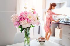 Modern kitchen decorated with pink peonies. Housewife cooking dinner. Interior design stock photos