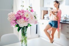 Modern kitchen decorated with pink peonies. Woman having coffee and relaxing using phone. Interior design royalty free stock images