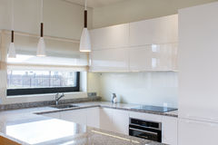 Modern kitchen design in light interior with wood accents. Stock Photos