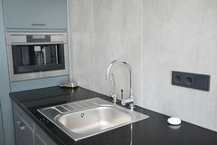 Modern kitchen with faucet and metal kitchen sink, electic stove royalty free stock photos