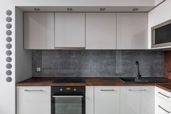 Modern kitchen with gray backsplash. Modern kitchen with granite worktop, gray concrete backsplash and functional white cabinets royalty free stock photo