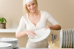 Modern kitchen - happy woman washing dishes Royalty Free Stock Photos