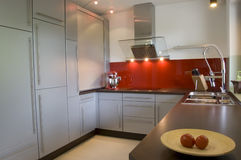 Modern Kitchen Interior. Modern kitchen with brand new stainless steel appliances, gray cupboards and a red glass feature wall Stock Photos