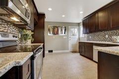 Modern kitchen interior with dark brown storage cabinets Stock Image