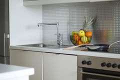 Modern kitchen interior. A frying pan standing on a stove and a bowl with fruits standing on table in a modern kitchen Royalty Free Stock Photography
