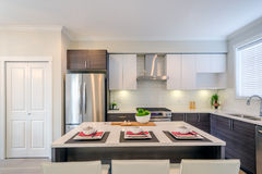 Modern kitchen interior. With island and cabinets in a luxury house set for dinner Stock Photos
