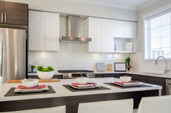 Modern kitchen interior. With island and cabinets in a luxury house set for dinner Stock Image
