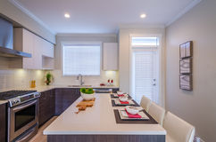 Modern kitchen interior. With island and cabinets in a luxury house set for dinner Royalty Free Stock Photos
