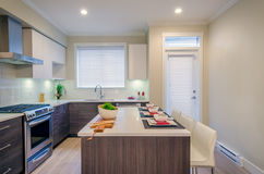 Modern kitchen interior. With island and cabinets in a luxury house set for dinner Royalty Free Stock Images