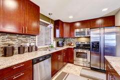 Modern kitchen interior with mosaic back splash trim and granite. Modern kitchen interior with bright wooden cabinets and steel appliances. Mosaic back splash stock photos