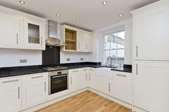 Modern kitchen L shape kitchen in white. Brand new modern L shape kitchen unit with appliances in white Royalty Free Stock Photos
