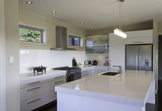 Modern Kitchen. A large white modern kitchen with stainless steel accessories Royalty Free Stock Photography