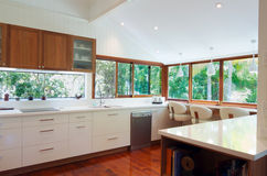 Modern Kitchen. Luminous modern kitchen with white and wooden cabinets, large windows with green views and polished wooden floors Stock Images