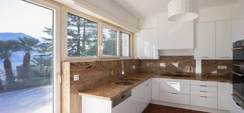 Modern kitchen with marble top and lake view stock photography