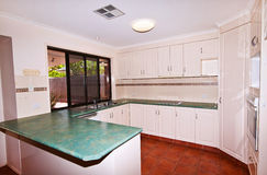 Modern Kitchen Overlooking Pool. A modern kitchen with views of the pool and gardens Royalty Free Stock Photos