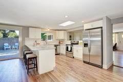Modern kitchen room interior in white tones with hardwood floor. Royalty Free Stock Images