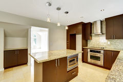 Modern kitchen room with matte brown cabinets and granite trim. Royalty Free Stock Photography