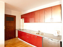 Modern kitchen. With single drainer sink and mixer tap, red drawer and cupboard units, polished wooden floor with white walls and ceiling Royalty Free Stock Photography