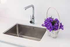 Modern kitchen sink and faucet with decorative flowers. Kichen stock photography