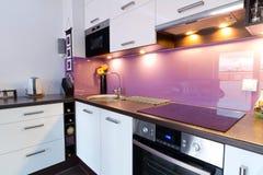 Modern kitchen with spotlights. Modern white and purple kitchen interior stock photos