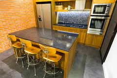 Modern Kitchen. Stylish modern contemporary kitchen with island bar, chair and home appliances Stock Image
