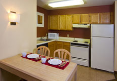 Studio Apartment Kitchen Dining Living Space. Modern kitchen, table, and appliances in resort hotel Stock Photos