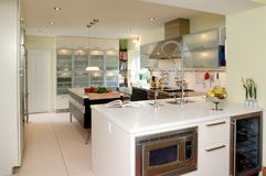 Modern kitchen with white counter top. Modern kitchen with white marble counter top and wine cellar royalty free stock photography