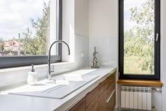 Kitchen worktop with sink. Modern kitchen with white worktop, elegant sink and big window stock images