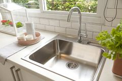 Modern kitchen with white worktop sink. And big window stock photos