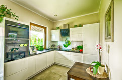 Modern kitchen wide angle HDR image. Wide angle view of an elegant modern kitchen royalty free stock photography