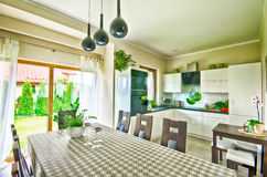 Modern kitchen wide angle HDR image. Wide angle view of an elegant modern kitchen and dining room table Stock Image