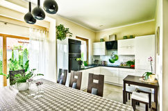 Modern kitchen wide angle HDR image. Wide angle view of an elegant modern kitchen and dining room table stock images