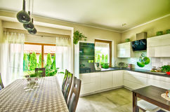Modern kitchen wide angle HDR image. Wide angle view of an elegant modern kitchen and dining room table Royalty Free Stock Images