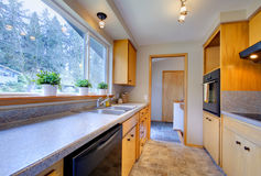 Modern kitchen with wide window. Modern kitchen with wooden cabinets, tile floor and wide window royalty free stock images