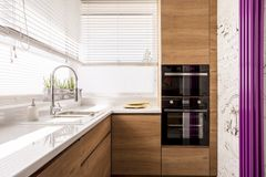 Modern kitchen with wood accents. An iron sink, and two chopping boards next to a microwave, and an oven Royalty Free Stock Photos